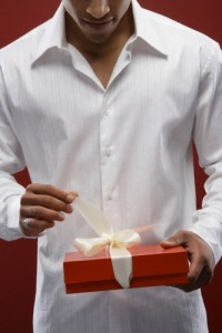 Mixed race man opening wrapped gift